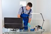 picture of janitor  - Portrait Of Male Janitor Cleaning Desk In Office - JPG