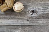 Old Baseball Mitt With Used Ball On Rustic Wood