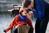 stock photo of child feeding  - Father feeding disabled son a hamburger in wheelchair - JPG