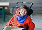 foto of wheelchair  - Handsome happy biracial eight year old boy smiling in wheelchair outdoors - JPG