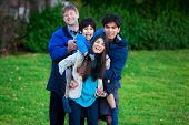 stock photo of biracial  - Disabled biracial child riding piggy back on his sister family surrounding him together at park.