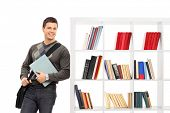 Male student leaning on a bookshelf isolated on white background
