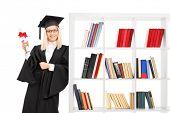 Female graduate leaning on a bookshelf isolated on white background