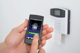 foto of keypad  - Security Alarm Keypad With Person Arming The System With Remote Controller - JPG