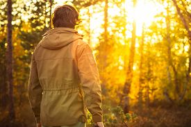 stock photo of boy scout  - Young Man standing alone in forest outdoor with sunset nature on background Travel Lifestyle and survival concept - JPG