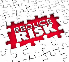 image of risk  - Reduce Risk words in the hold of a puzzle with missing pieces to illustrate the need to lower dangers and increase safety and security - JPG