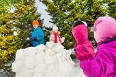 pic of snowball-fight  - Back of girl throw snowball while standing opposite the snow wall with boy and girl during beautiful winter day in the forest