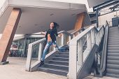 image of staircases  - Gorgeous young brunette in jeans jumping from a staircase - JPG