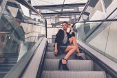 picture of mini-skirt  - Gorgeous young brunette in black skirt posing on an escalator - JPG