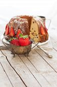 image of icing  - Rustic style bundt cake with raisins decorated with strawberries and sprinkled with icing sugar - JPG