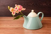 foto of teapot  - Light blue teapot with flowers on a wooden background  - JPG