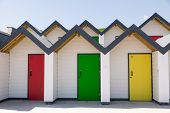 stock photo of beach-house  - Colourful doors of yellow red and green with each one being numbered individually of white beach houses on a sunny day in Swanage - JPG