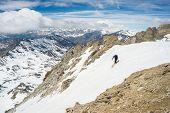 foto of italian alps  - One unrecognizable person skiing downhill on steep snowy slope - JPG