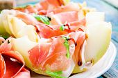 picture of melon  - salad of fresh melon with thin slices of prosciutto arugula leaves and balsamic sauce closeup - JPG