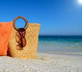 image of hot-water-bag  - straw bag towel anad sunglasse by the shore - JPG