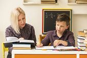 stock photo of tutor  - Schoolboy do homework at home with a tutor - JPG