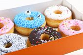 foto of donut  - delicious and tempting box full of donuts with different flavors and toppings in unhealthy nutrition and sugar and sweet cake addiction concept - JPG