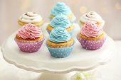 pic of cake stand  - Delicious cupcakes on cake stand on table on light background - JPG
