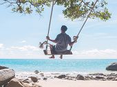 pic of swing  - Young man swinging in a swing on tropical summer beach - JPG
