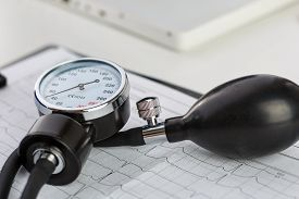 stock photo of manometer  - Medical manometer lying on cardiogram chart closeup. Medical help prophylaxis disease prevention or insurance concept. Cardiology carehealth protection and prevention. Healthy life concept ** Note: Visible grain at 100%, best at smaller sizes - JPG