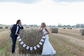 pic of married  - Married couple standing with the elbows on a hay bale that is written  - JPG