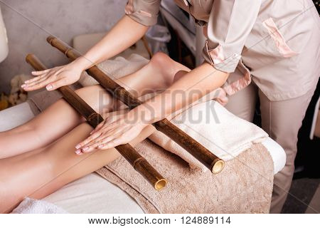 poster of Massage of human foot in spa salon with bamboo sticks.