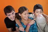 image of teen pony tail  - Young girl touching bubble from her brothers chewing gum on orange background - JPG