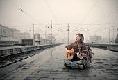 Woman sitting on the platform of a train station and singing and playing guitar