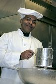 foto of flour sifter  - african american male baker sifting flour and grinning mischieviously  - JPG