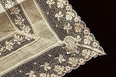 stock photo of macrame  - Closeup of detail of Irish linen handkerchief on black velvet - JPG