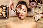 Beautiful young girl getting chocolate mask in spa salon poster