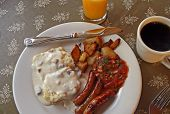 stock photo of biscuits gravy  - homestyle breakfast of biscuits and gravy with sausage and potatoes