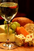 stock photo of gourmet food  - glass of white wine and assorted cheeses for wine tasting - JPG