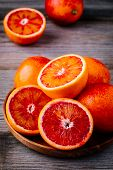 Sliced And Whole Ripe Juicy Blood Oranges And Grapefruit In The Box On Wooden Background. poster