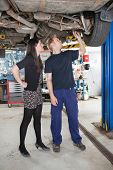 Young male mechanic and woman looking at underboy of car in auto repair shop