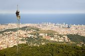 Man working in antenna with Barcelona city view in front of him