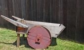 Old rickety wood wheelbarrow with a red wheel sitting on grass with weathered fence in background