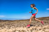 Fit woman athlete trail running in outdoor desert. Side view of Asian girl runner jogging outside. F poster