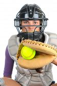 Closeup of a female softball catcher wearing a mask and chest protector holding glove with ball in t