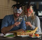 Carnival couple celebrating at sushi restaurant wearing carnival masks. poster