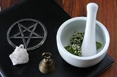 stock photo of magickal  - closeup of wicca spell tools and book of shadows with crystal bell mortar and pestle - JPG