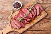 Slices Of Medium Rare Roast Beef Meat On Wooden Cutting Board, Pepper And Rosemary Branches On Woode poster