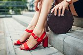 Stylish Shoes And Accessories. Young Woman Wearing Fashionable Red High-heeled Sandals And Holding H poster