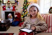 Front view close up of a young Caucasian girl wearing a Santa hat sitting on the sofa using a tablet poster