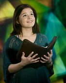 A beautiful young teen before a large stained glass window looking heavenward with an opened Bible.