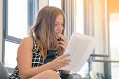 The Girl Reads A Letter With Good News Sitting On The Couch. Woman Enjoying Good News In Writing. An poster