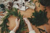 Making Rustic Christmas Wreath Flat Lay. Hands Holding Fir Branches, And Pine Cones, Thread, Berries poster