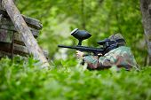 Paintball player in camouflage and protective mask with marker sits in ambush in the green grass behind shelter.