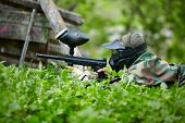 Paintball player in camouflage and protective mask with marker lies in ambush in the green grass.