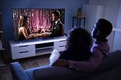 Affectionate Young Family Watching Tv At Home poster